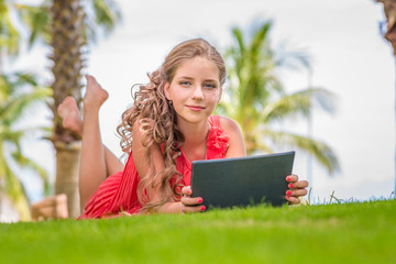 Smiling young girl with digital tablet laying on grass. Palm trees on background.