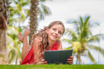 Smiling young girl with digital tablet laying on grass and dreamy looking away. Palm trees on background.