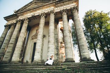Beautiful romantic wedding couple of newlyweds hugging near old castle