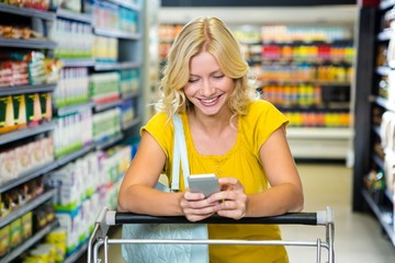 Smiling woman with cart using smartphone