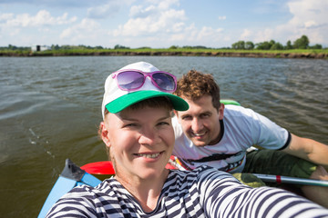 Young people doing selfie during kayaking on river in beautiful nature