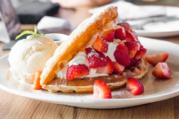 Strawberries waffles with vanilla ice cream on white plate.