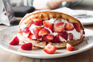 Strawberries waffles with vanilla ice cream on white plate.
