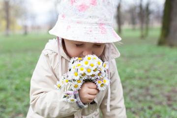 Little girl smelling spring flowers