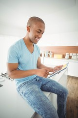 Smiling man using tablet in the kitchen sitting on counter