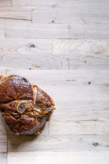 beautiful grilled slice of an organic leg of lamb meat on a oak tree cutting board seen from above