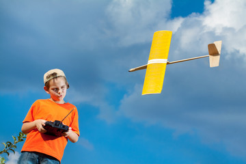 Little boy playing with handmade RC airplane toy