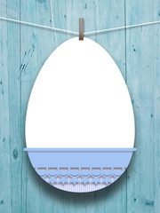 Close-up of hanged blank decorated Easter egg with peg against aqua wooden boards background