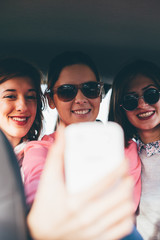 Portrait of three friends taking photos with a smartphone in car