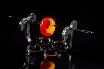 Orange and red glass bead on stand