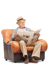 Senior reading a newspaper seated on armchair