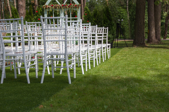 White wedding chairs on a green lawn, without decoration-2