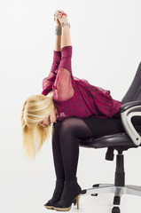 Beautiful young woman stretching arms and back in office chair, exercise at work