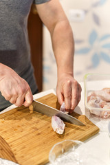 man preparing chicken wings to cook them