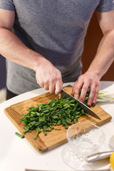 man chopped green onion on the board. Wooden table