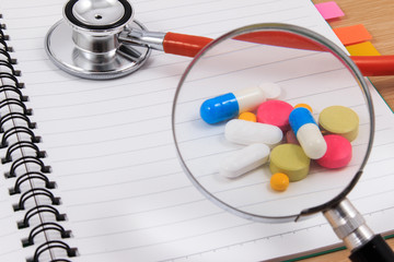 Stethoscope, magnify and many colorful pills on blank notepad.