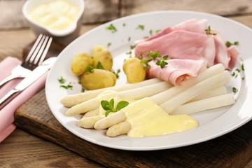Gekochter Spargel an heller Sauce mit Schinken und Kartoffeln auf weißem Teller serviert