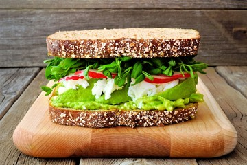 Superfood sandwich with avocado, egg whites, radish and pea shoots on whole grain bread against a rustic wood background