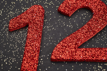 Number twelve red color over a black background. Anniversary