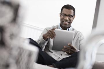 A man sitting on a sofa, using a digital tablet,