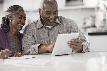 A senior couple seated at a table side by side, using a digital tablet, looking at the screen,