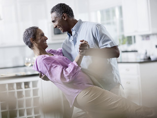 An affectionate mature African American couple, with their arms around each other dancing,
