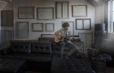 Loft decor, A wall hung with pictures in frames, reversed to show the backs, A man playing a guitar,