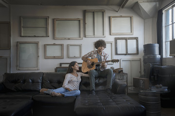 Loft decor, A wall hung with pictures in frames, reversed to show the backs, A man playing a guitar and a woman sitting on a sofa,