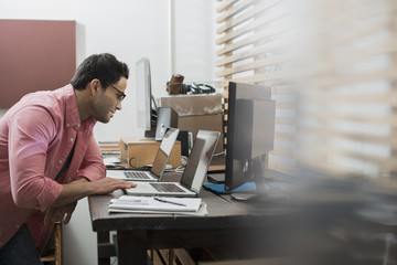 A man in a home office with a desk with two laptops, checking information on the screen,