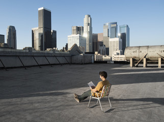 A man sitting in a beach chair on a city rooftop reading,