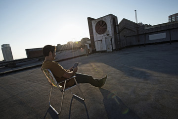 A man sitting in a beach chair on a city rooftop, using a digital tablet,