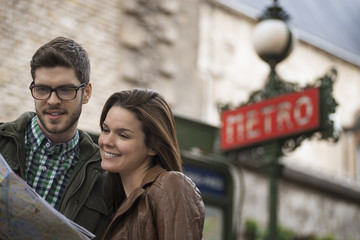 Couple consulting map on city street, under classic Art Deco Metro sign in Paris, France