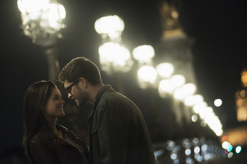 A couple embracing and kissing in a city at night under the streetlights,
