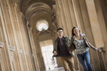 A young couple walking down a colonnade in the historic heart of a city,