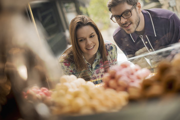 A couple looking at the window display in a confectionery shop,