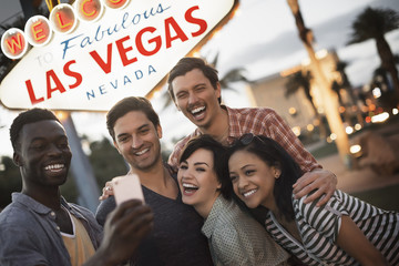 A group of five friends, men and women posing under the Las Vegas sign,