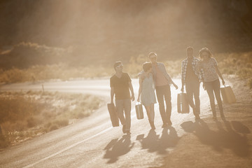 A group of people, men and women, on the road with cases, in open country in the desert,