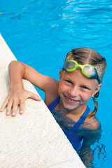 Portrait of little cute girl in the swimming pool. Sportime