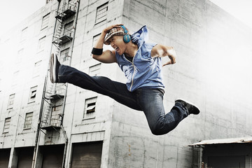 A young man doing a karate kick, one leg outstretched and one leg bent up, wearing earphones,