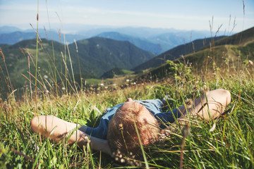 Man lying in high green grass on the mountain medaow