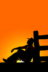 silhouette of cowboy sit by post look up