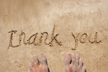 Conceptual thank you text handwritten in sand
