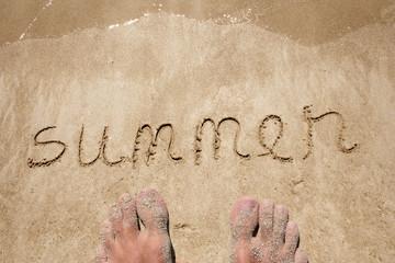 Conceptual summer text handwritten in sand