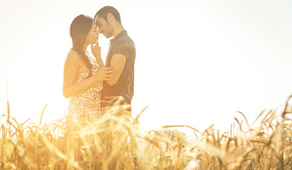 Young couple kissing in a wheat field