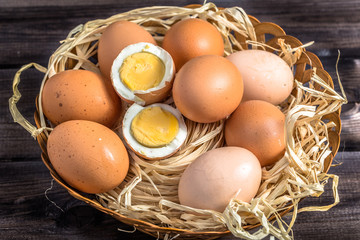 Eggs in basket on wooden table.