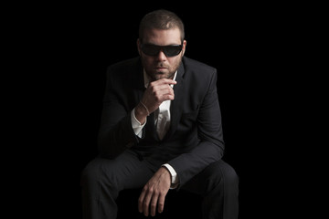 portrait of a tough cool man with sunglasses on balck background