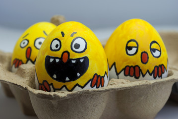 Chicken peeking out of an egg shell with different faces in a packet