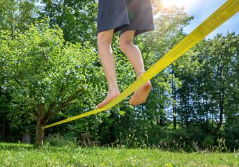 Kind balanciert barfuß auf Slackline im Garten