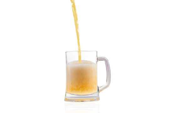 Beer pouring into half full glass isolated over white background