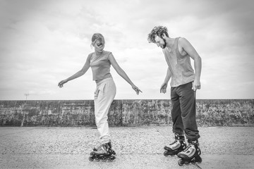 Friends learn rollerblading together have fun at park.